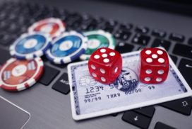Laptop mit sympolischen Würfeln und Kreditkarte - Onlineglücksspiel